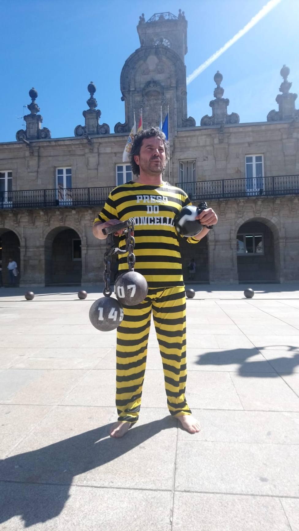 El propietario de una librería protesta con cadenas y vestido de preso por impagos del Concello
