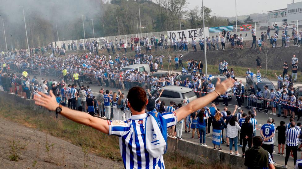 Aficionados de la Real Sociedad despiden al equipo en Zubieta antes de volar a Sevilla. EFE