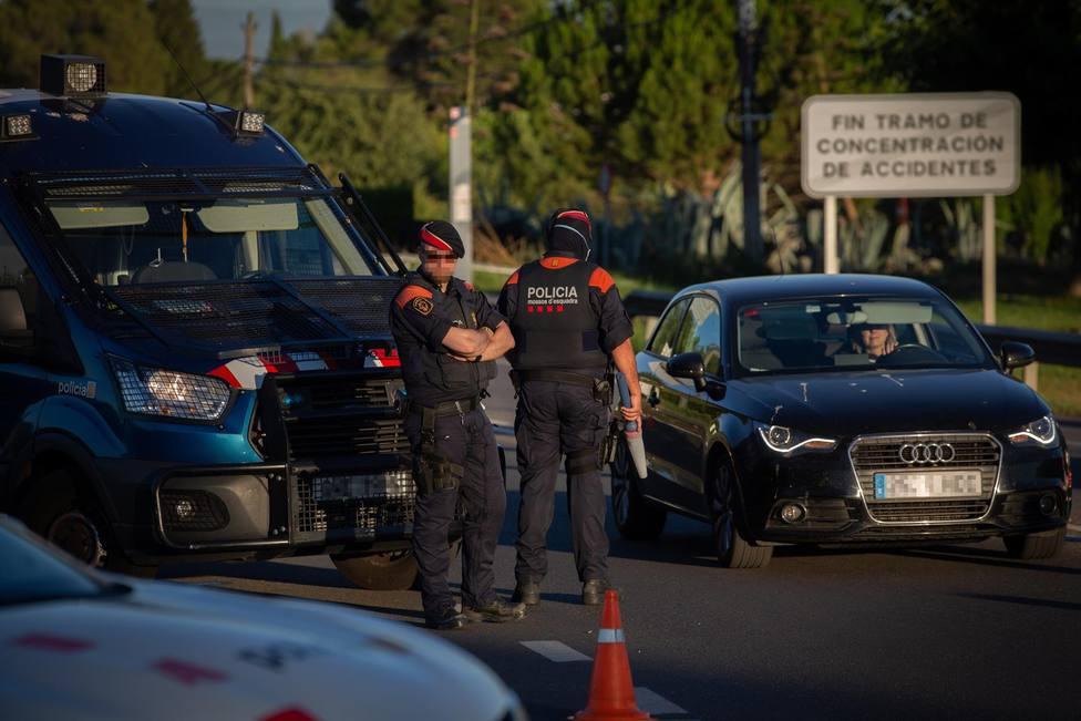 Un Mosso dEsquadra controla un acceso en carretera por las restricciones derivadas de la pandemia