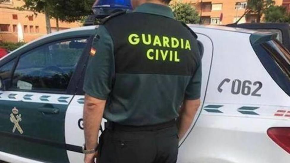 Un agente de la Guardia Civil junto a un vehículo oficial - ABC