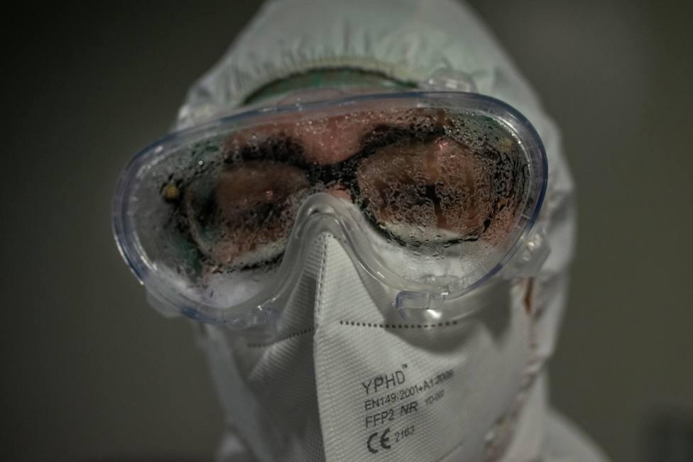 Un sanitario muestras su cara de cansancio tras atender una zona de afectados por coronavirus
