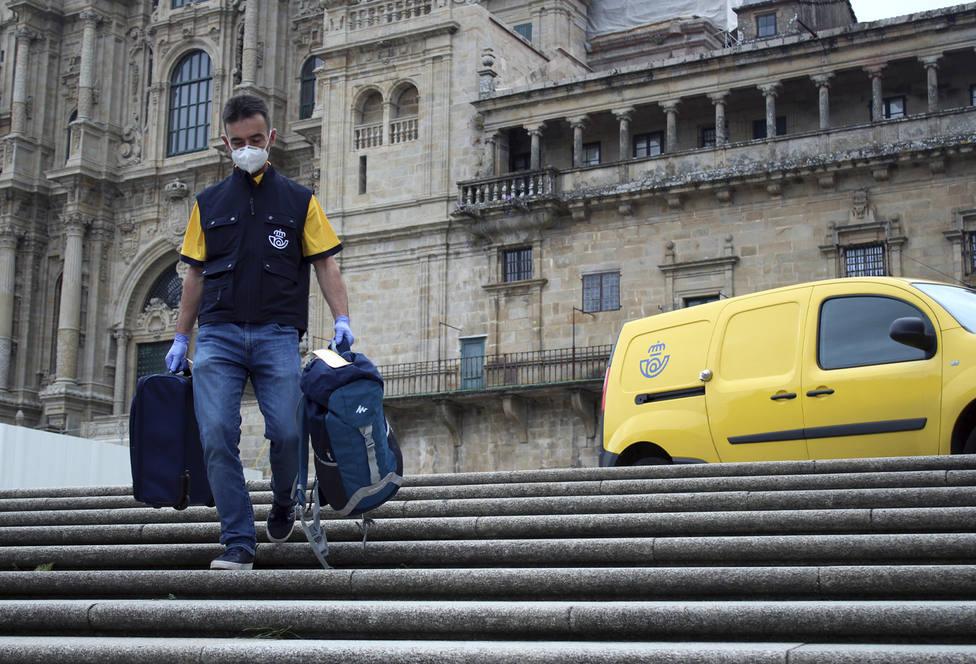 Un cartero portando una mochila en la plaza do Obradoiro, en Santiago - FOTO: Correos