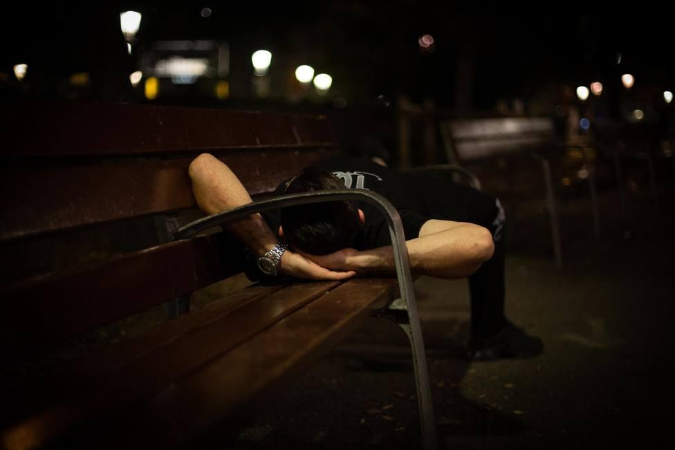 Un hombre duerme sobre un banco en la Plaza de Catalunya, a 10 de junio de 2021, en Barcelona, Catalunya (Espa