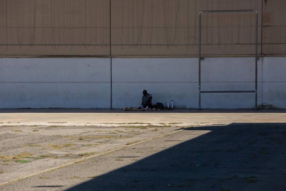Un hombre descansa a la sombra junto al albergue de temporeros en Fira de Lleida