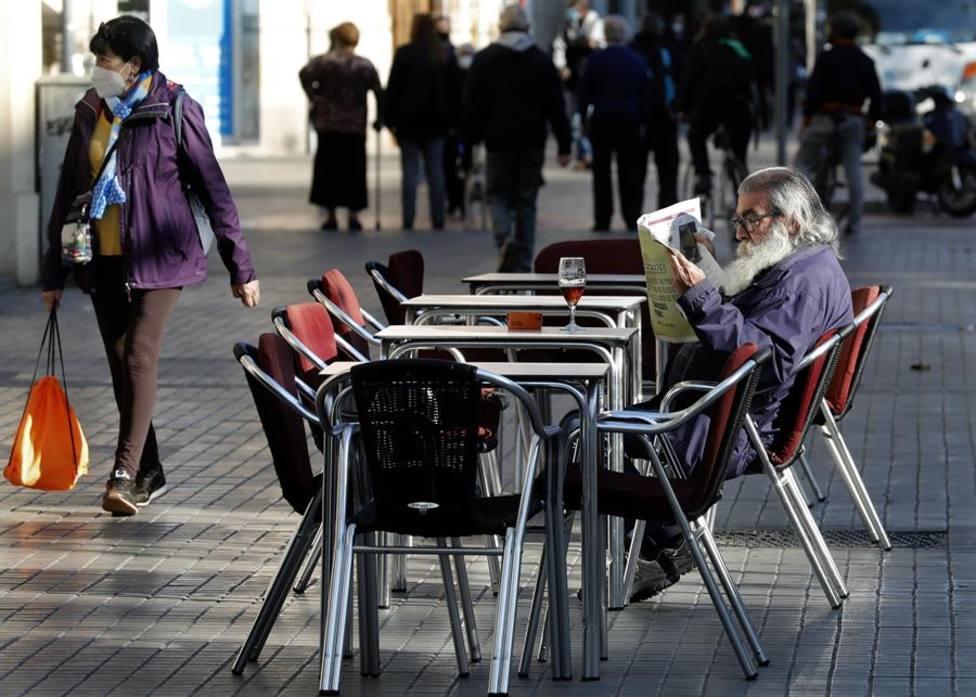 Un hombre lee un periódico en la terraza de un bar de Barcelona que han reabierto este lunes