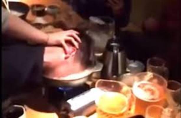 Un hombre mete el rostro de otro en una olla