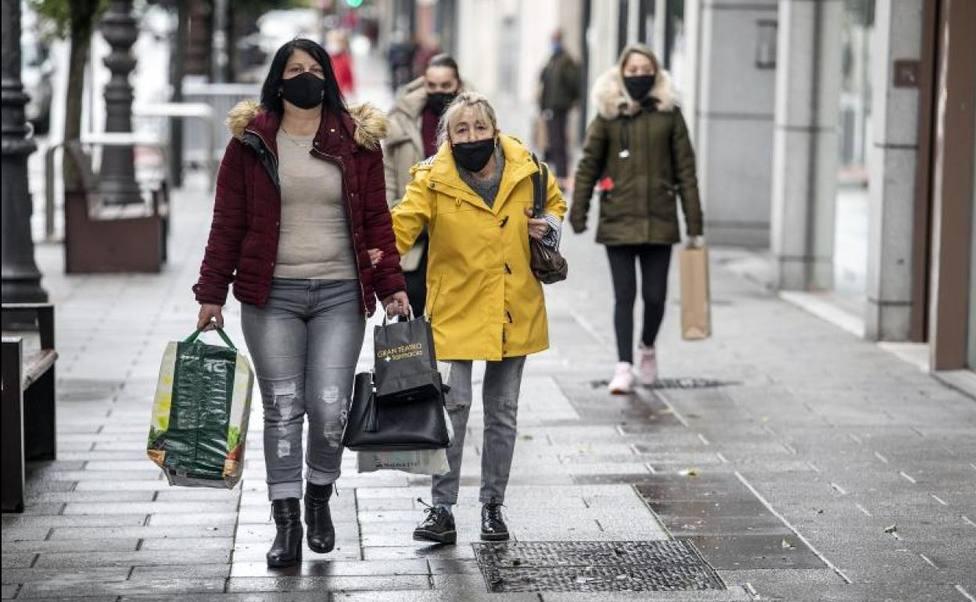 Mujeres caminan con mascarillas
