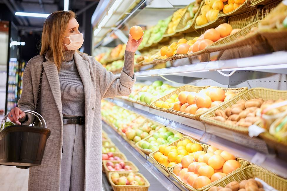 Woman in medical masks is shopping in grocery store during virus pandemic