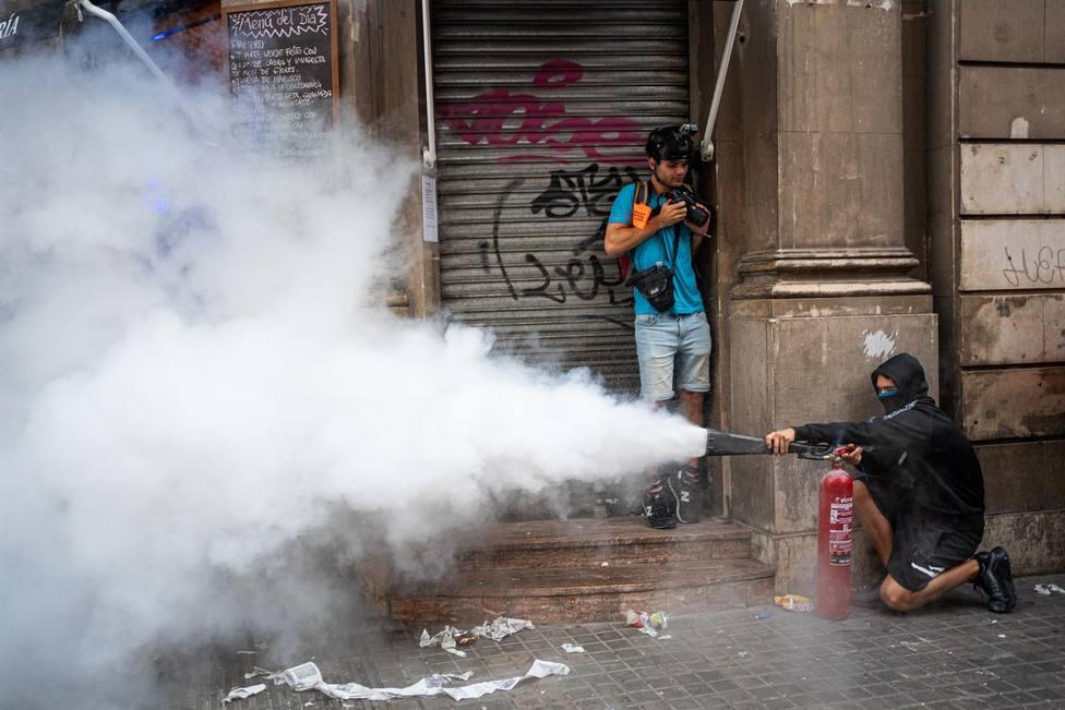 Un hombre rocía con un extintor a la policía durante los altercados en la comisaría de la Policía Nacional