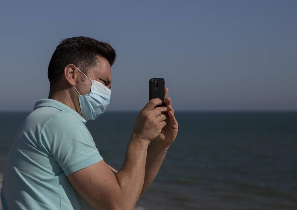 Un hombre con mascarilla hace una foto