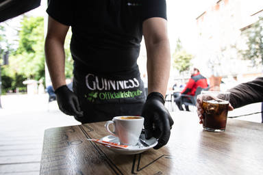 Un camarero sirve un café en una terraza