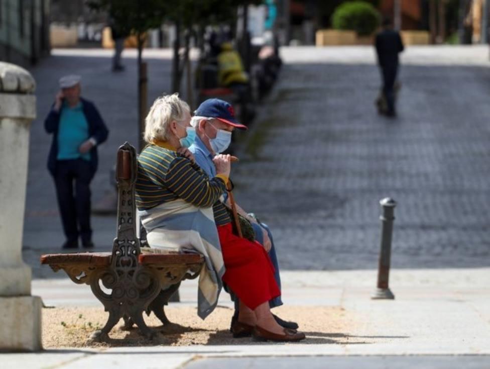 FOTO DE ARCHIVO: Personas mayores con mascarilla en un banco de un parque en Madrid, España