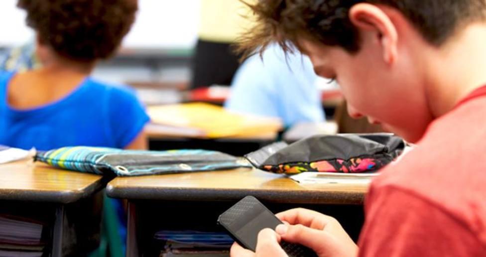 Imagen de archivo con un alumno en clase en pleno uso de su teléfono móvil, un debate abierto en las aulas del