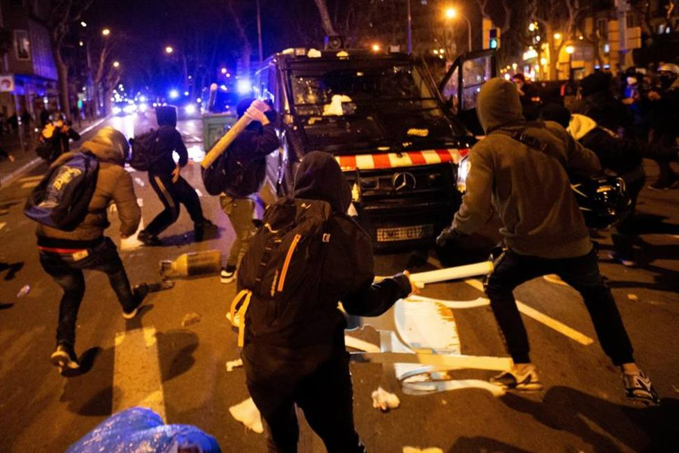 manifestantes lanzan objetos a un vehículo de los cuerpos antidisturbios