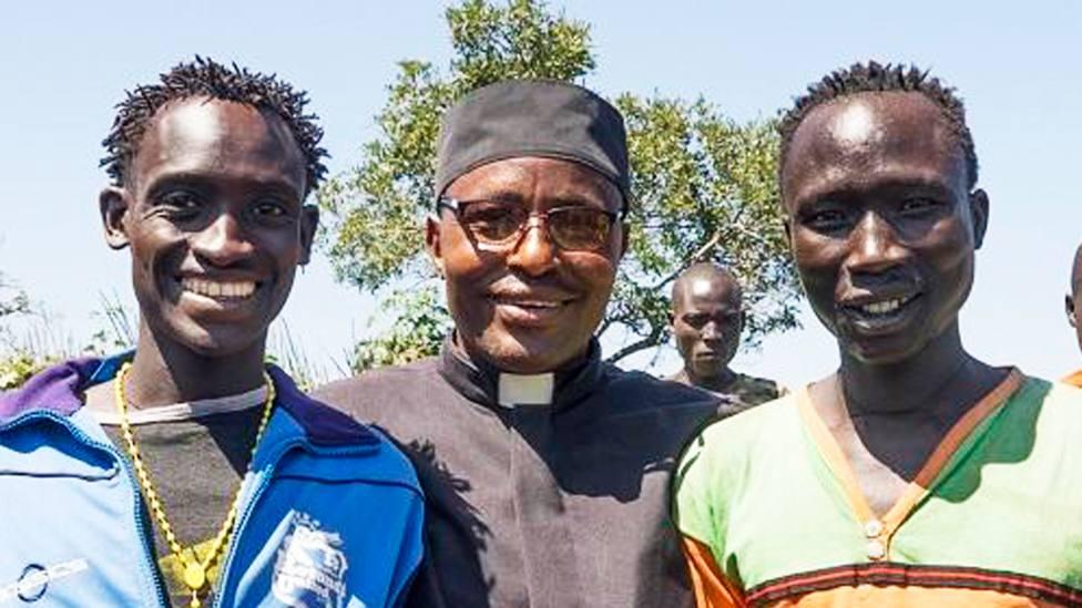 Dos miembros de la tribu Gumuz junto al sacerdote que los bautizó y confirmó