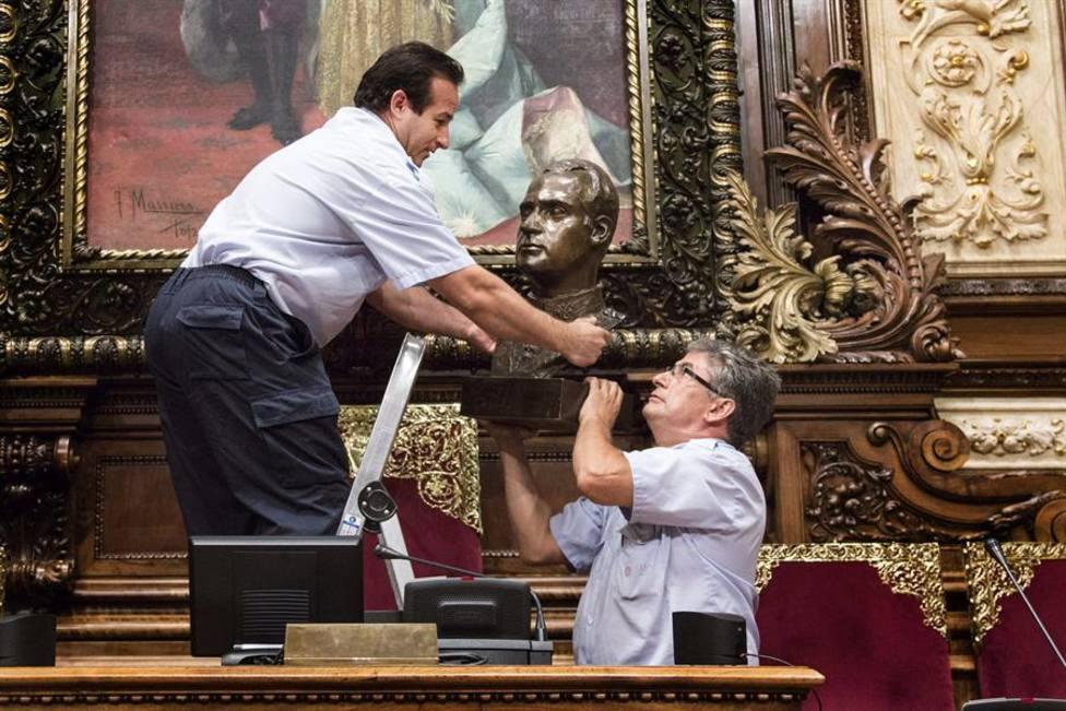 Dos operarios del Ayuntamiento de Barcelona retiran el busto de Don Juan Carlos en 2015