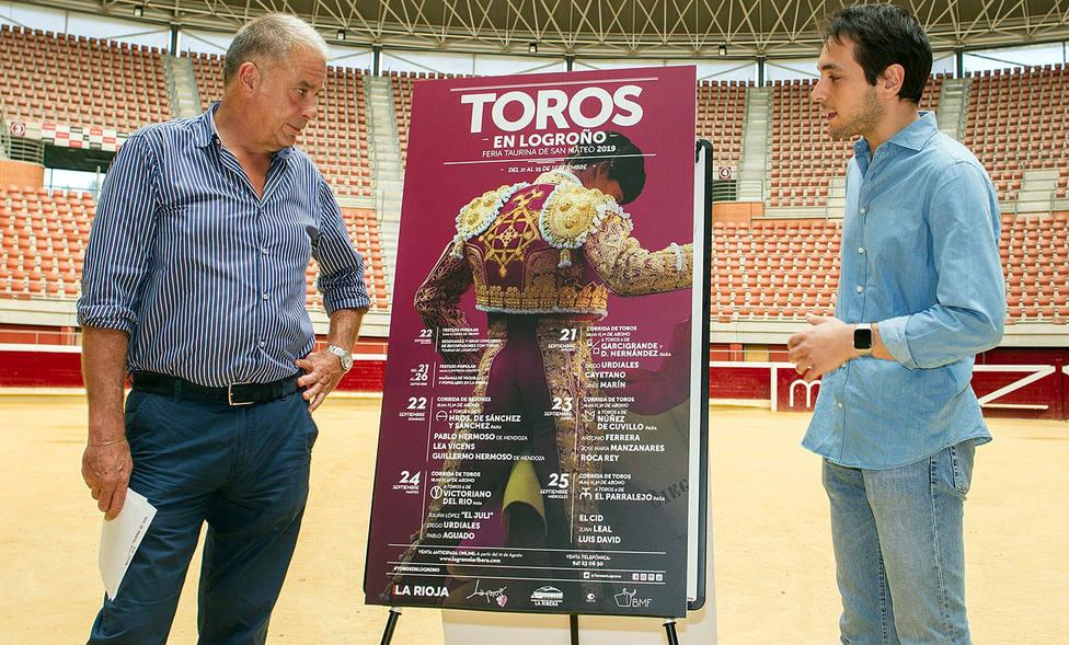 Óscar Chopera y su sobrino Manuel junto al cartel anunciador de la Feria de San Mateo de Logroño
