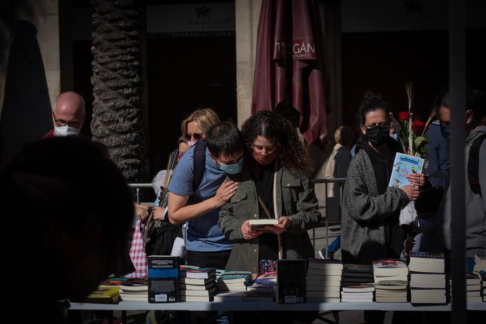 Dos jóvenes miran un libro en una parada de Sant Jordi en Barcelona - David Zorrakino - Europa Press - Archivo