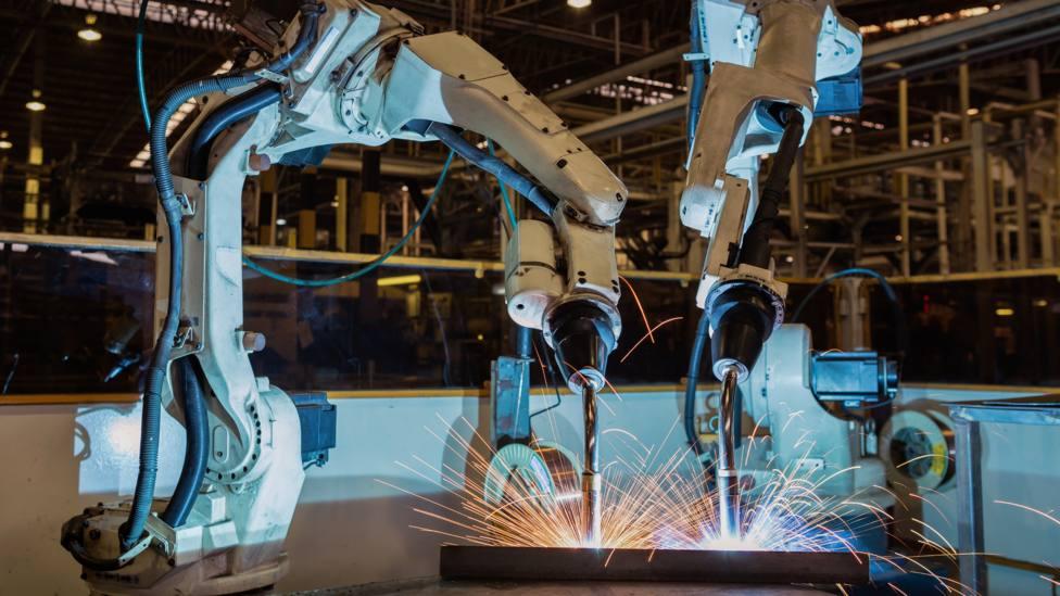 Foto de archivo de unos robots soldando