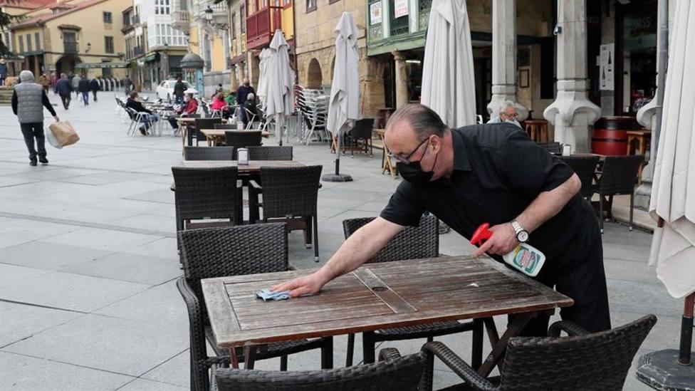 Un camarero desinfecta la mesa de una terraza del centro de Avilés