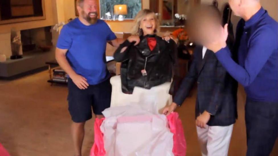 Momento en el que Olivia Newton John recibe su chaqueta de cuero de Grease tras ser subastada