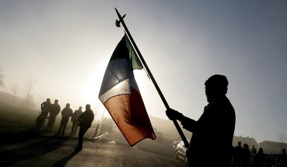 Un hombre levantando la bandera de Irlanda durante un acto homenaje
