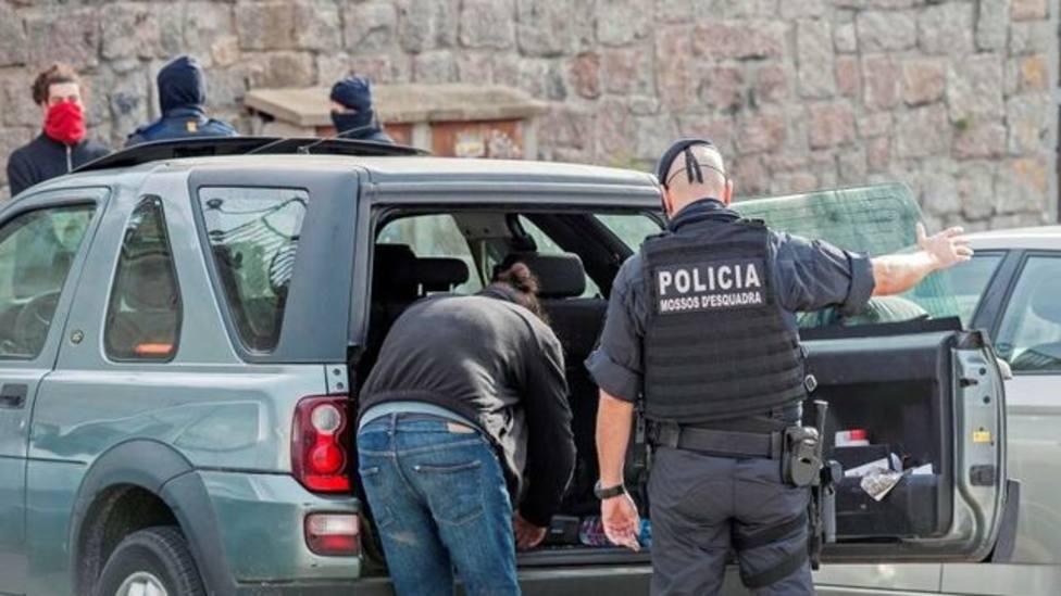 Un miembro del cuerpo de los Mossos d'Esquadra inspecciona el vehículo de una persona