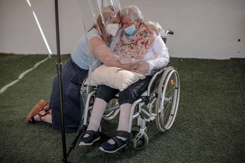 Una madre y su hija se abrazan con una cortina de plástico en una residencia de Valencia