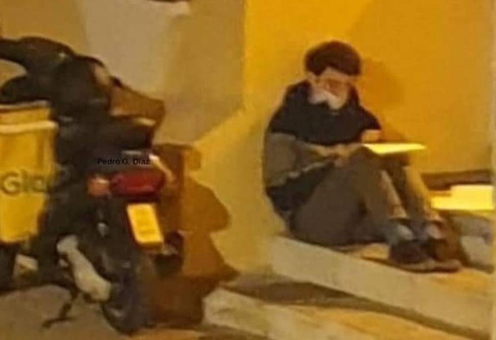 Un joven repartidor de Glovo estudia bajo la luz de una farola de Málaga mientras espera su próxima entrega