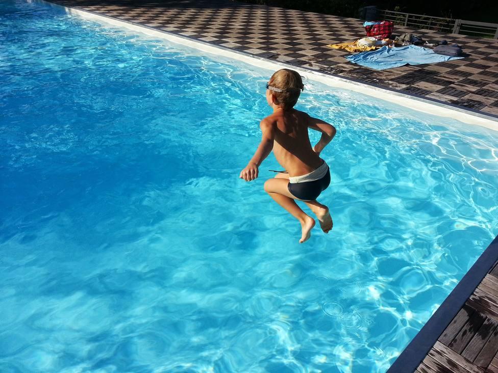 Foto de un niño lanzándose a una piscina