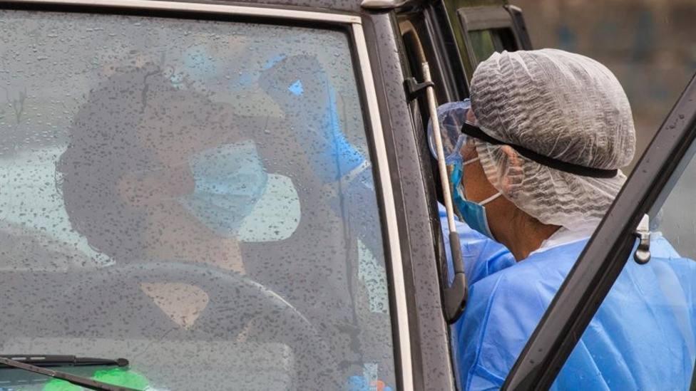Una enfermera toma una muestra para un PCR a un joven en Laviana