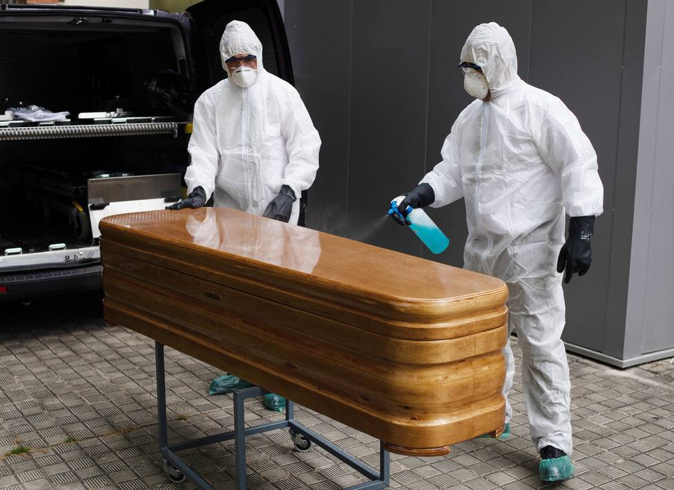 Operarios funerarios desinfectan un ataúd