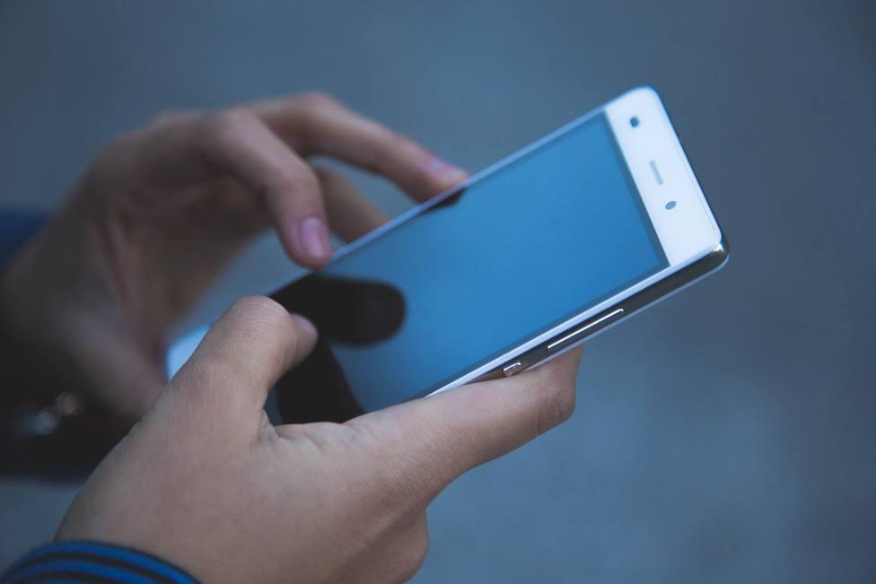 Un usuario manipulando un teléfono móvil