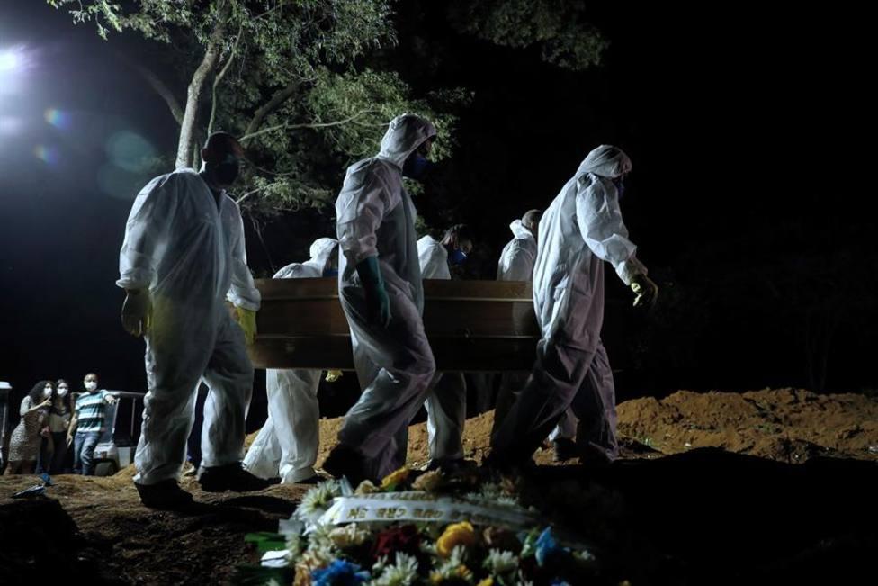 Fotografía que muestra el entierro nocturno de una víctima de la covid-19 hoy en el cementerio Vila Formosa e