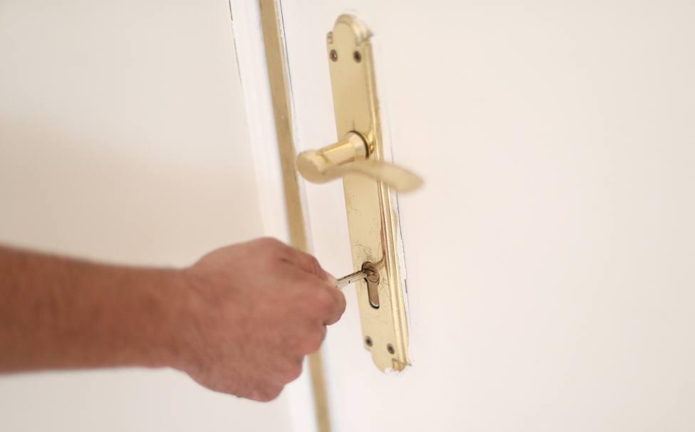 Un hombre introduce una llave en la cerradura de la puerta de una vivienda.