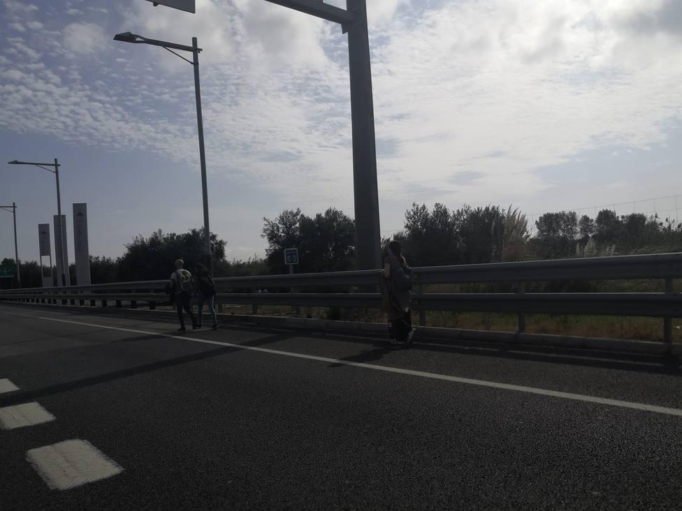 Centenares de personas, algunas con maletas, se dirigen caminando a la T1 del Aeropuerto de Barcelona