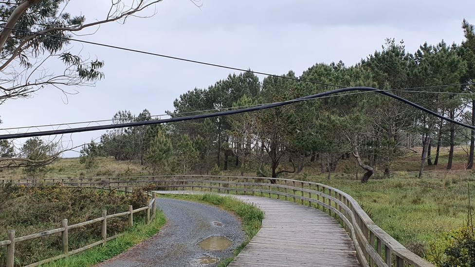 En el acceso a la playa de Esmelle los cables aparecen colgados - FOTO: Cedida