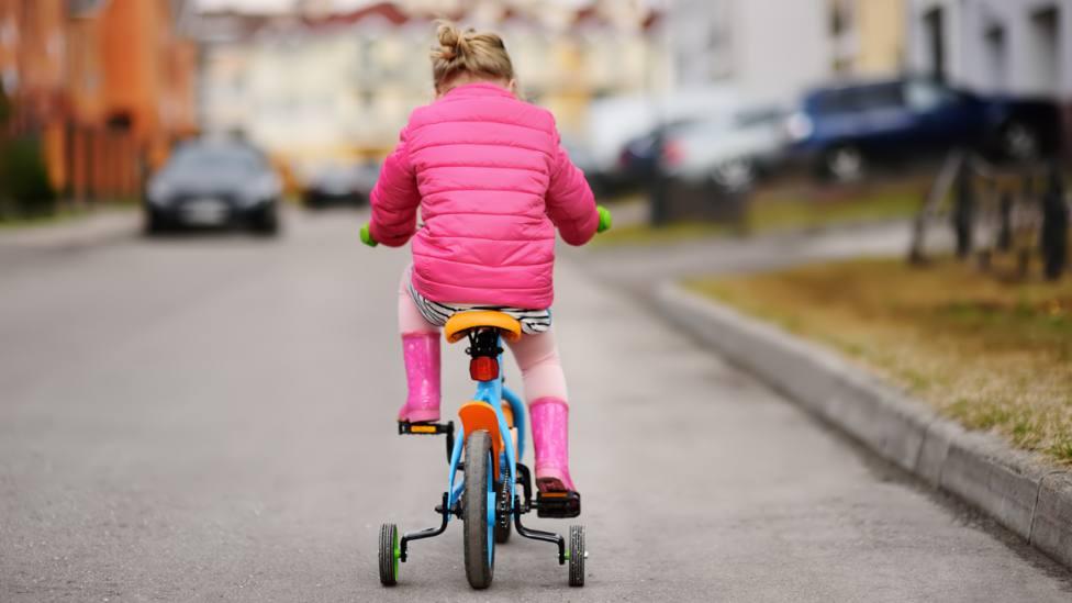 Foto de archivo de una niña disfrutando de su bicicleta en una zona urbana