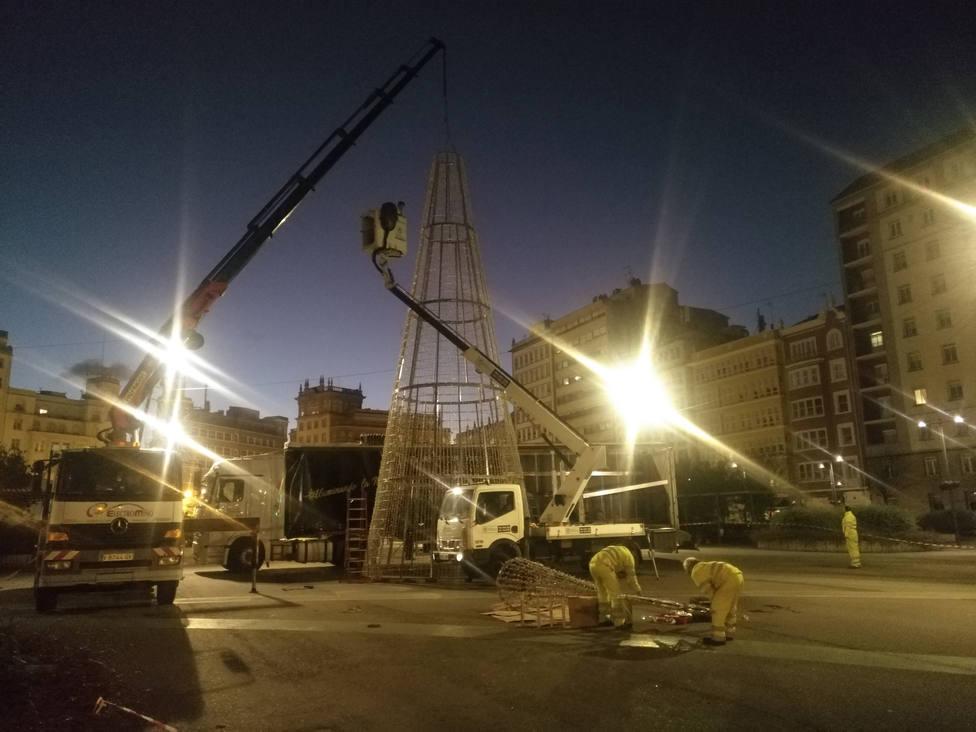 Operarios colocando un árbol de Navidad en la plaza de España este lunes