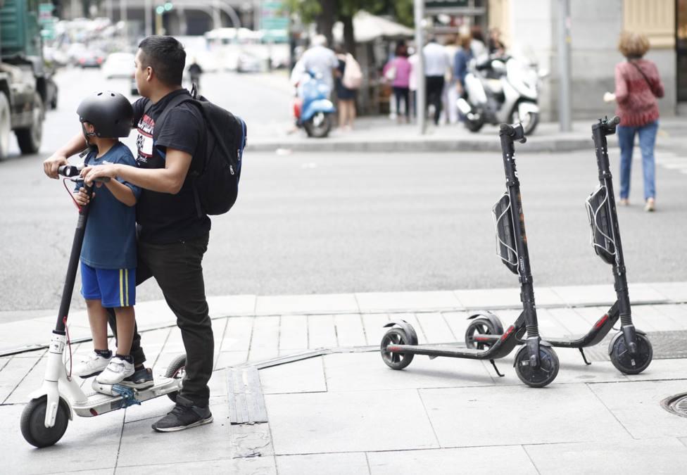 Un niño y un adulto montando en un patinete eléctrico en la calle Goya de Madrid - Europa Press - Archivo