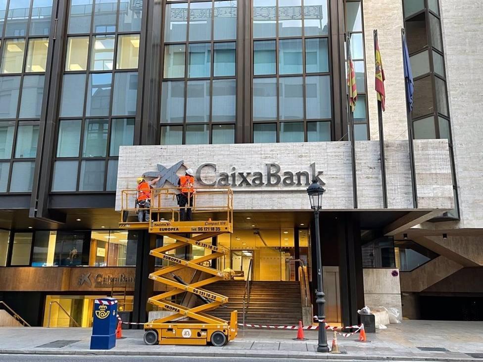 Operarios colocan el logo de CaixaBank en el edificio que albergaba la sede de Bankia en Valencia