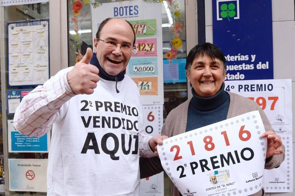 """Los propietarios de la papelería """"Julcar"""" de Valladolid, muestran el número 21816, segundo premio de la loterí"""