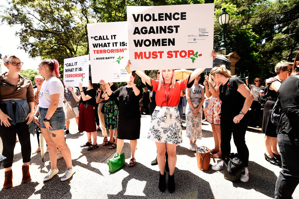 Protesters hold placards during a domestic violence protest organised by The Red Rose Foundation in Brisbane, Friday, February 21, 2020. (AAP Image/Albert Perez) NO ARCHIVING