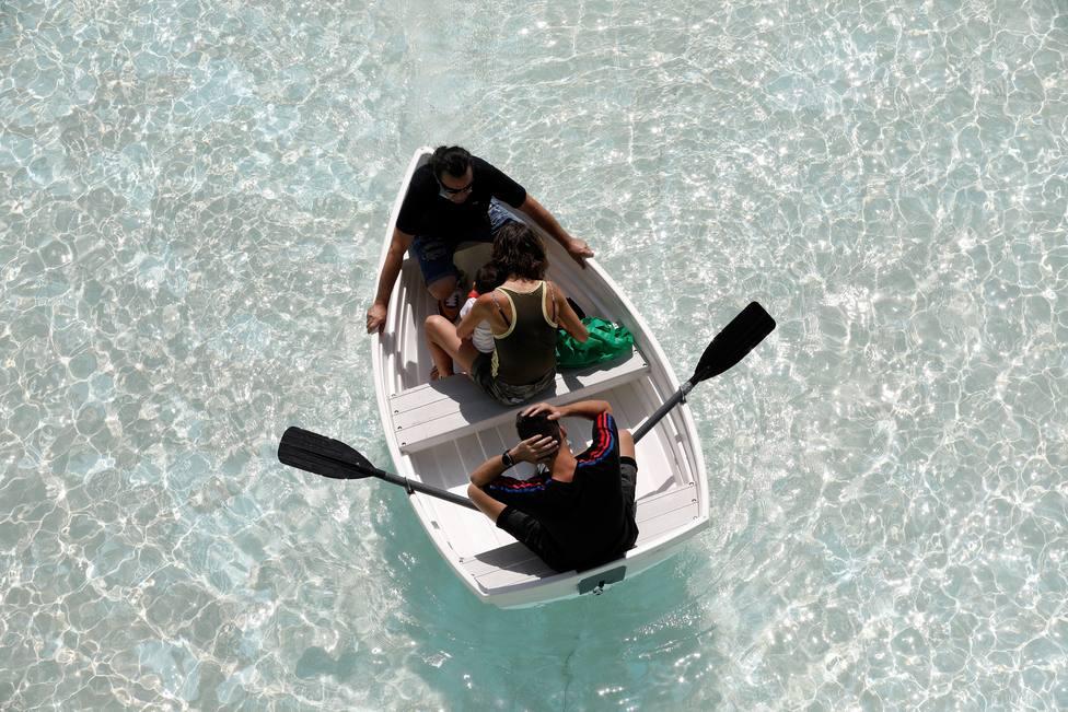 Personas refrescándose en el lago de la Ciudad de las Artes y las Ciencias de Valencia