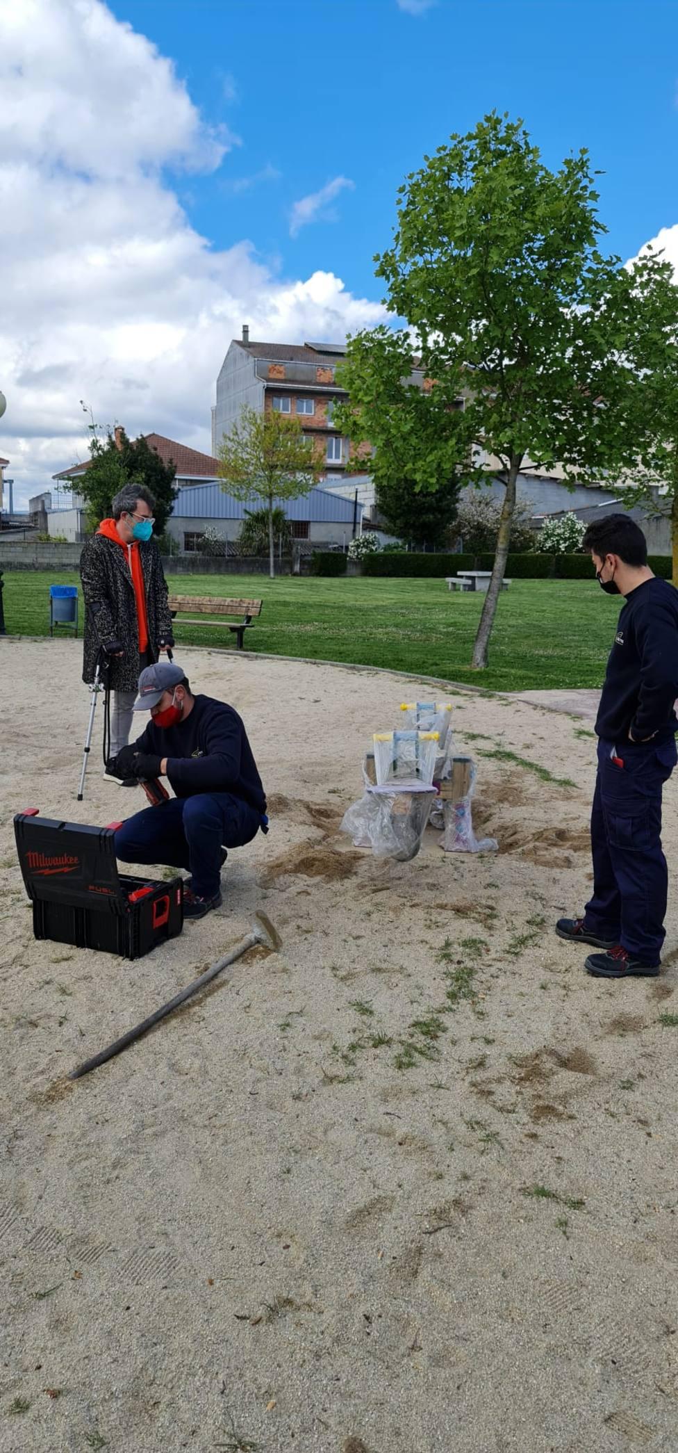 Operarios municipales reparando la zona de juego en un parque de Xinzo
