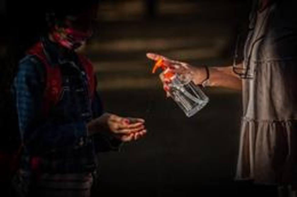 Una profesora administra gel desinfectante a un alumno en un colegio
