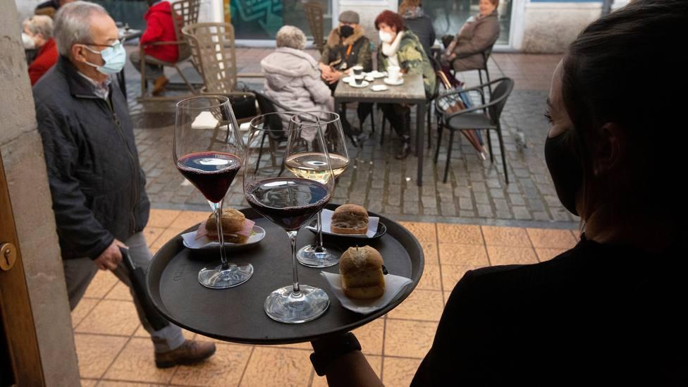 Una camarera se dispone a servir en una terraza de Avilés