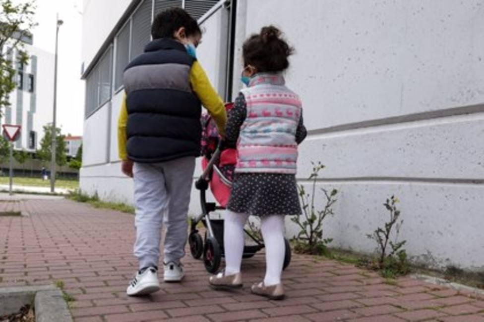 Dos niños paseando por la calle con mascarillas - JESÚS HELLÍN - EUROPA PRESS
