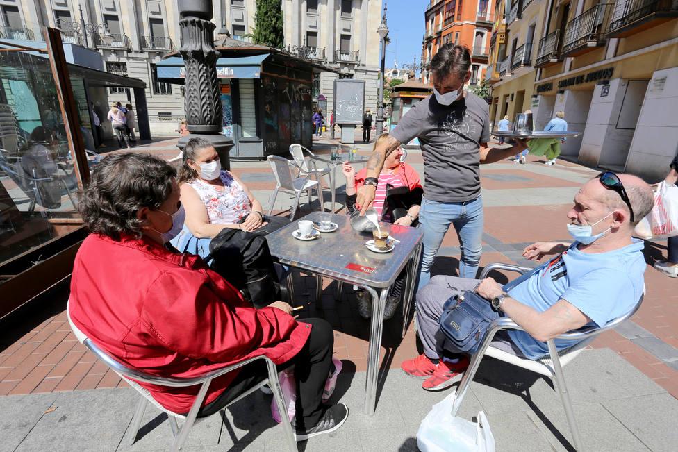 Un hostelero atiende a un grupo de clientes en su terraza, en Valladolid