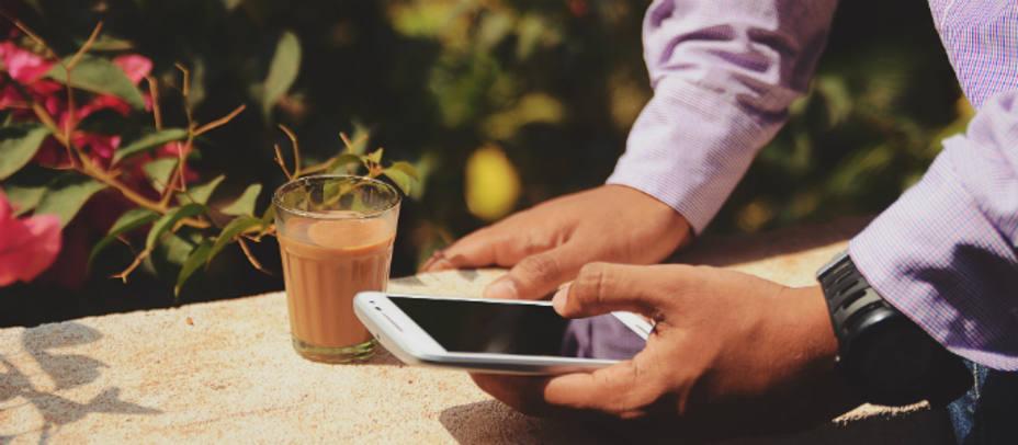 Imagen de un hombre tomando un café junto a su móvil. Foto de archivo